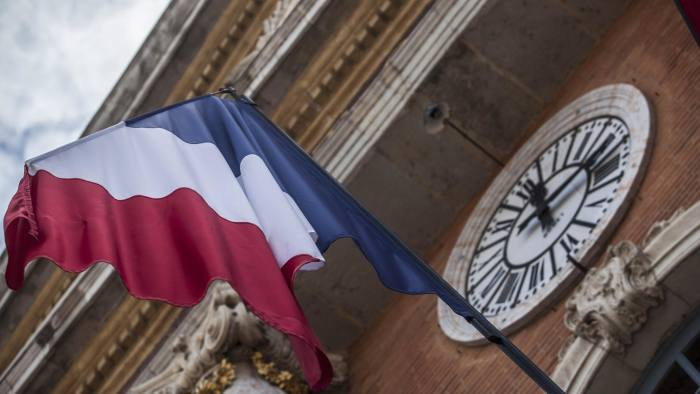 The national flag of France flies beneath a clock in Toulouse, France, on Tuesday, Aug. 12, 2014. The euro traded 0.3 percent from a nine-month low before reports this week that may show growth in the region weakened and inflation slowed, adding to signs the bloc's economy is struggling to recover. Photographer: Balint Porneczi/Bloomberg