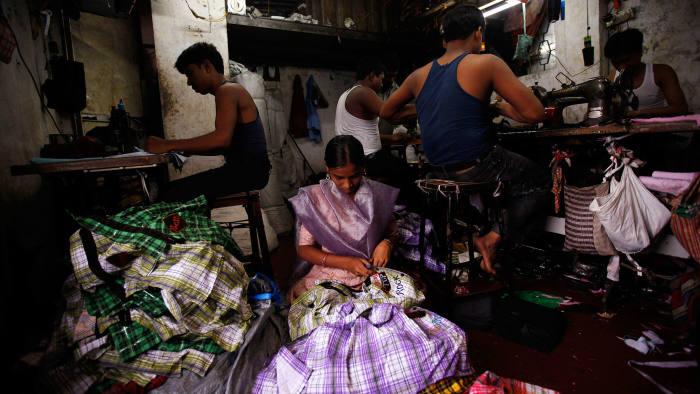 Fifteen-year-old Saira (centre) cuts shirt threads inside a garment factory in Mumbai August 3, 2010