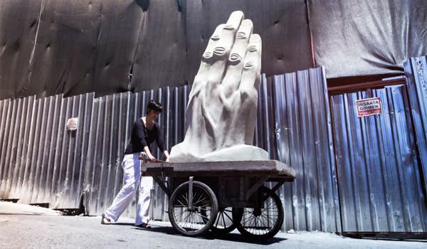 A woman pushing a cart bearing a sculpture of huge white hands