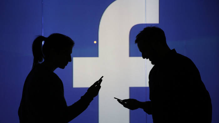 People are seen as silhouettes as they check mobile devices whilst standing against an illuminated wall bearing Facebook Inc.s logo in this arranged photograph in London, U.K., on Wednesday, Dec. 23, 2015. Facebook Inc.s WhatsApp messaging service, with more than 100 million local users, is the most-used app in Brazil, according to an Ibope poll published on Dec. 15. Photographer: Chris Ratcliffe/Bloomberg