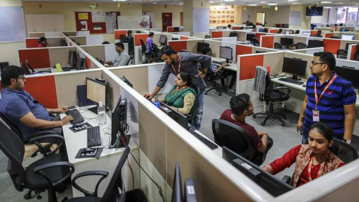 Employees work at a call center servicing Xiaomi Corp. in Bengaluru, India, on Friday, March 31, 2017. Once compared with Apple Inc. for its sleek smartphones and charismatic leadership, Chinese startup Xiaomi is seeking an image makeover as it tries to recover from a sales-growth slide. Photographer: Dhiraj Singh/Bloomberg