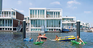 Children playing in the water near floating homes in IJburg, Amsterdam