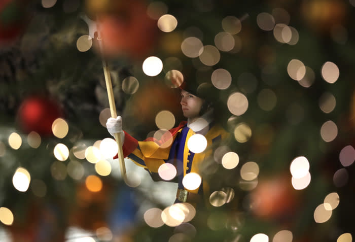 A Swiss guard is framed by Christmas tree lights as Pope Francis holds his weekly general audience in the Paul VI Hall at the Vatican, Wednesday, Dec. 20, 2017. (AP Photo/Alessandra Tarantino)