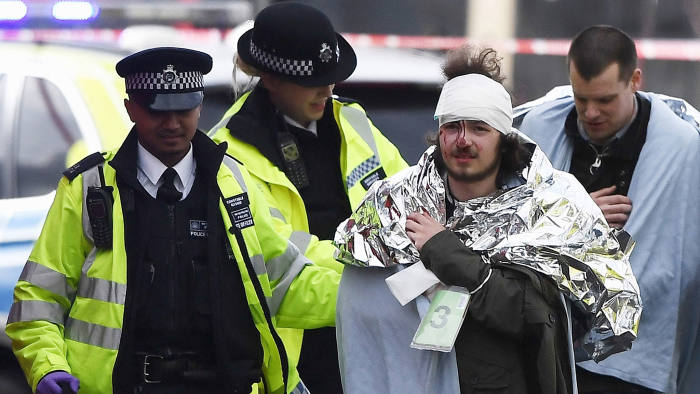 A member of the public is treated by emergency services near Westminster Bridge and the Houses of Parliament on March 22, 2017 in London, England