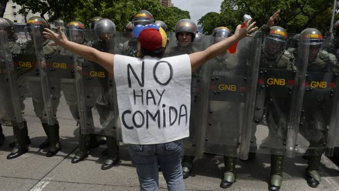"""A woman with a sign reading """"There is no food"""" protests against in front of a line of policemen in Caracas"""