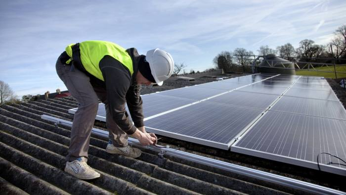 Jake Beautyman installs solar panels on a barn roof on Grange farm, near Balcombe. The installation is part of an initiative by local residents in Balcombe to encourage more people to use renewable energy rather than energy based on carbon such as fracking. The initaitive is called Repowerbalcombe and is supported by the charity 10:10. (Photo by In Pictures Ltd./Corbis via Getty Images)