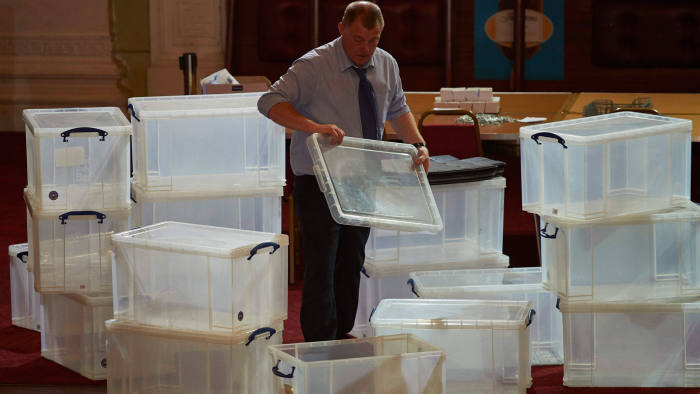 An election official stacks plastic boxes at a vote counting centre in Margate, southeast England