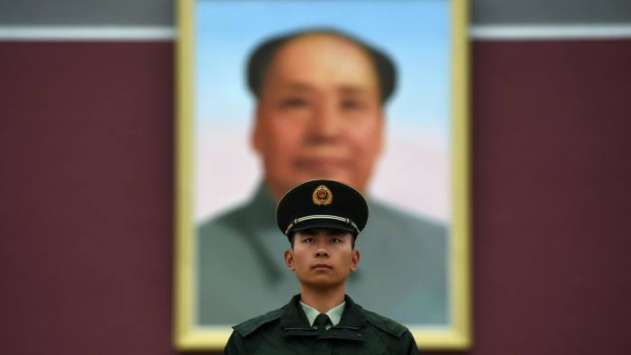 A paramilitary police officer stands guard in front of the portrait of late communist leader Mao Zedong on Tiananmen Gate in Beijing on China's National Day, October 1, 2014. Crowds visited the square on the 65th anniversary of the founding of Communist China, by late revolutionary leader Mao Zedong. AFP PHOTO/Greg BAKER (Photo credit should read GREG BAKER/AFP/Getty Images)