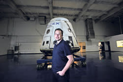 Elon Musk, founder of SpaceX, in front of one his company's space capsules