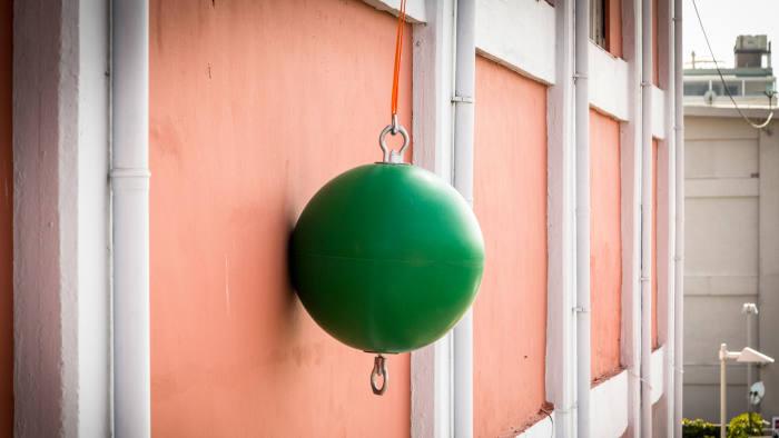 An art installation of a huge green ball on a rope beside a wall by Ayse Erkmen