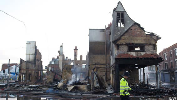 A police officer walks past the charred remains of Reeves furniture store in Croydon