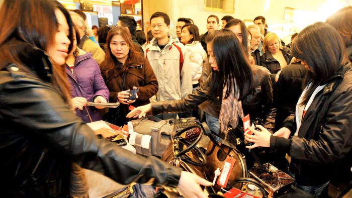 Shoppers grab at handbags reduced by 50% from just over a thousand pounds, in the handbag section of the Selfridges store in Oxford Street central London, as the start of the Selfridges sale gets under way. PRESS ASSOCIATION Photo. Picture date: Friday December 26, 2008. Hundreds of shoppers queued outside stores today waiting to snap up a bargain in the seasonal sales