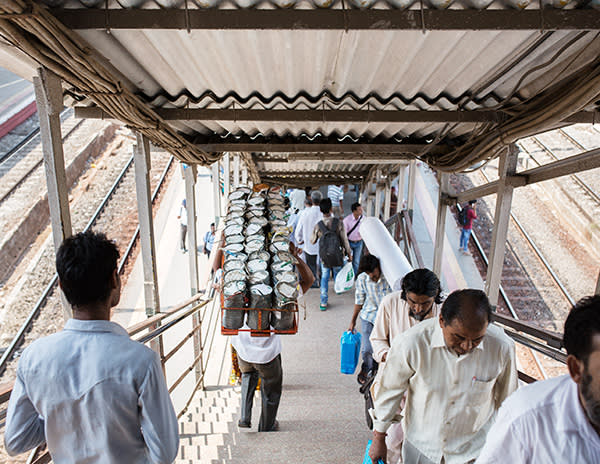 Dashrat Kedari carries tiffin boxes down the stairs at Santacruz station