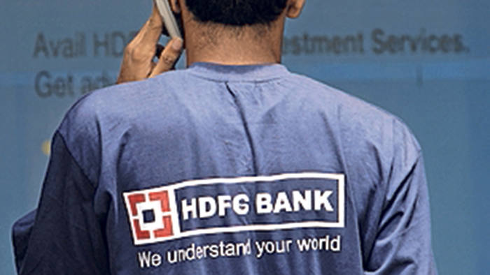An employee of HDFC Bank Ltd., talks on his mobile phone outside a bank branch in Mumbai, India, on Tuesday, July 10, 2007