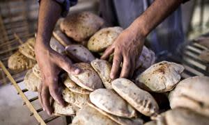 A worker arranges freshly baked bread in a bakery in Cairo, Egypt, on Sunday, May 19, 2013. Egypt will curb wheat imports by 31 percent to 8 million metric tons in 2012-13, still enough to make it the world's biggest buyer, the U.S. Department of Agriculture estimates. Photographer: Shawn Baldwin/Bloomberg