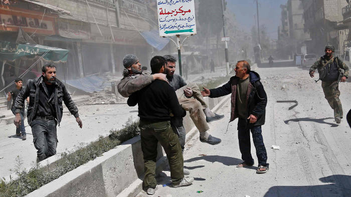 Syrians carry an injured man following a reported government air strike on the rebel-controlled town of Hamouria, in the eastern Ghouta region on the outskirts of the capital Damascus, on April 3, 2017. / AFP PHOTO / ABDULMONAM EASSAABDULMONAM EASSA/AFP/Getty Images