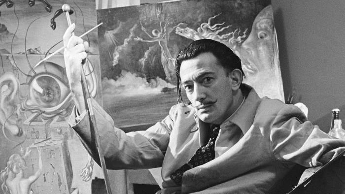 NEW YORK - 1943: Surrealist artist Salvador Dali poses with his oil paintings at his studio on the 8th floor of the Zeigfeld Theatre in 1943 in New York City, New York. (Photo by Michael Ochs Archives/Getty Images)