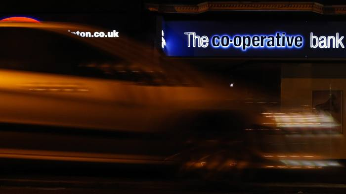 "An automobile passes a Co-Operative Bank Plc branch, a unit of Co-Operative Group Ltd., at night in Manchester, U.K., on Sunday, Dec. 14, 2014. Co-Op Bank Chief Executive Officer Niall Booker earlier this month said it ""would come as no surprise"" if the bank didn't meet the Bank of England's minimum capital requirements when the results of the stress test are released on Dec. 16, which models how banks would fare in another financial crisis. Photographer: Paul Thomas/Bloomberg"