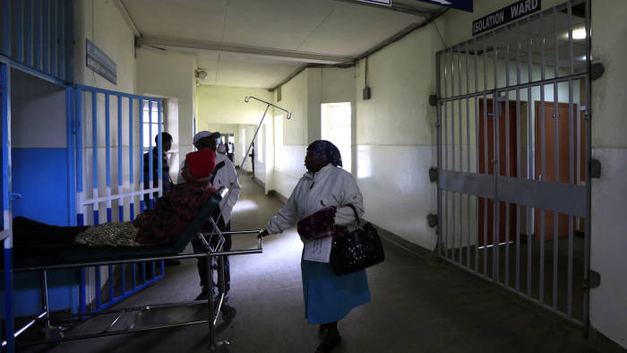 A patient is wheeled on a stretcher next to an isolation ward (R) set aside for Ebola related cases at the Kenyatta National Hospital (KNH) in the capital Nairobi August 19, 2014. Kenya Airways will suspend flights to Liberia's capital Monrovia and Sierra Leone's capital Freetown due to the Ebola outbreak in West Africa, the company said on Saturday. The suspension of the flights will start at midnight on Tuesday August 19, Kenya Airways said in a statement. Kenya will not allow passengers from Liberia, Guinea and Sierra Leone into the country starting Tuesday, the private Citizen Television said on its website, quoting the Minister of Health James Macharia. REUTERS/Noor Khamis (KENYA - Tags: HEALTH POLITICS TRANSPORT) - RTR42XFW