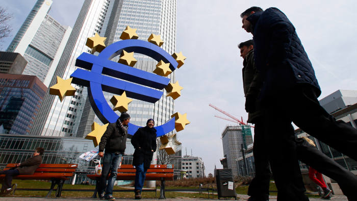 Pedestrians pass a euro sign sculpture outside the European Central Bank (ECB) headquarters in Frankfurt, Germany, on Thursday, April 4 2013