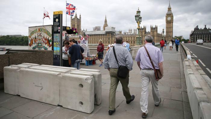 Pedestrians walk through newly installed barriers on Westminster Bridge in London, Monday, June 5, 2017