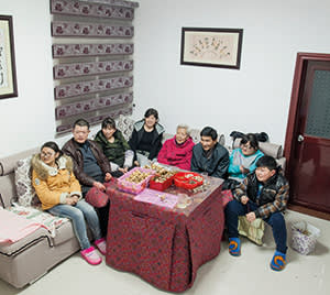 Xiang Ju's family watching TV and eating fruit and nuts in the family apartment in Shennongjia