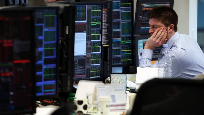 A trader reacts as he monitors financial information on computer screens on the trading floor at Panmure Gordon & Co. in London, U.K., on Friday, Jan. 22, 2016. At least 40 stock markets around the world with a total value of $27 trillion are in bear territory, as investors witness the worst start to a year on record. Photographer: Chris Ratcliffe/Bloomberg