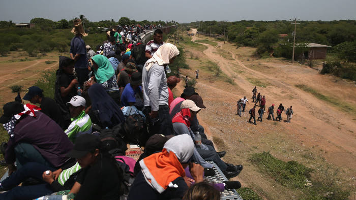 Migrants atop a train known as 'the Beast' as they travel across Mexico