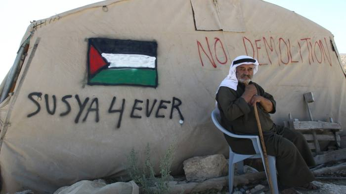 """A Palestinian man sits outside his tent in the southern West Bank village of Susya on July 22, 2015. Israel's High Court ruled in May that Susya's 340 residents could be relocated and its structures demolished, which Human Rights Watch derided as """"a grave breach"""" of Israel's obligations to the Palestinian populace under its military rule. The Israeli army has refused to say when it plans to demolish the new Susya, but said it can legally do so at any time, in accordance with the court ruling. AFP PHOTO / HAZEM BADER (Photo credit should read HAZEM BADER/AFP/Getty Images)"""