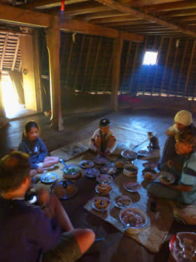 John Aglionby and family sit down to dine in one of the 'mbaru niang' houses