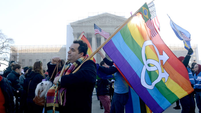A supporter of same-sex marriage rights, Marcos German-Domingues (C) holds his dog Sophia and a rainbow flag outside the US Supreme Court