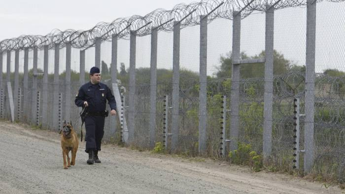 FILE - In this April 28, 2017 file photo a police officer with a dog patrols along the border fence on the Hungarian-Serbian border near Roszke, 180 kms southeast of Budapest, Hungary. The Hungarian government is proposing a set of laws that would tax and possibly sanction Hungarian groups who assist illegal migration and receive foreign funding. Interior Minister Sandor Pinter said Wednesday, Jan. 17, 2018 that such groups would have to register with the courts and pay a 25 percent tax on funds received from abroad. (Zoltan Gergely Kelemen/MTI via AP, file)