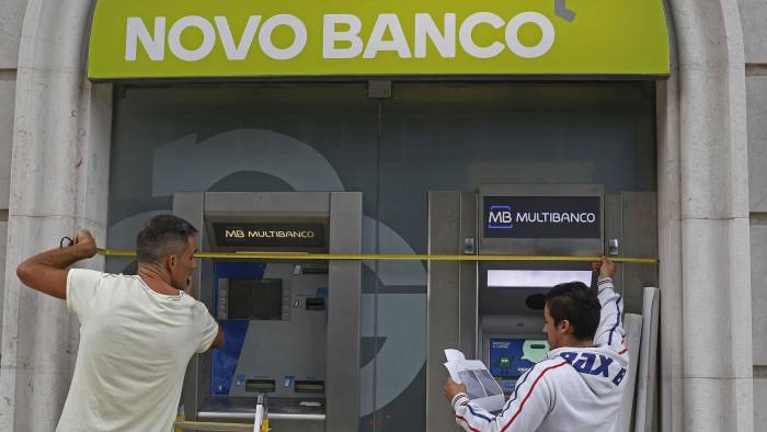 Workers install the new logo of Portuguese Novo Banco (New Bank) at their Lisbon office September 22, 2014. REUTERS/Hugo Correia (PORTUGAL - Tags: POLITICS BUSINESS) - RTR47A63