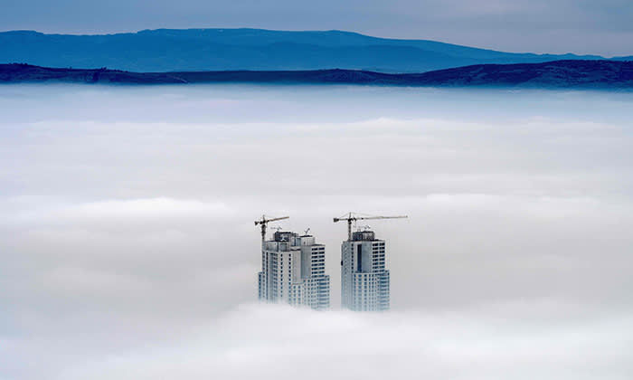 A picture taken from Vodno Mountain shows the tops of some of the city's highest buildings above clouds in an area with a high level of air pollution in Skopje on December 15, 2017. Skopje on December 15 was affected for the second day in a row by air pollution that almost paralyzed the Macedonian capital. / AFP PHOTO / Robert ATANASOVSKIROBERT ATANASOVSKI/AFP/Getty Images