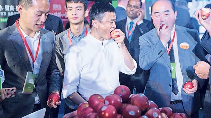 Alibaba chairman Jack Ma, center, tasted Washington apples at Alibaba Group Headquarters in Hangzhou, China on Oct. 14
