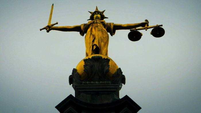 A statue of the scales of justice stands above the Old Bailey in London