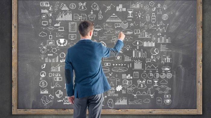 professor in front of blackboard writing symbols