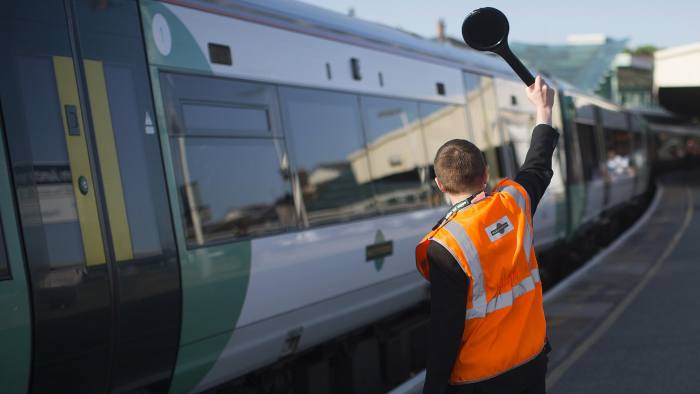 A Southern Railway Ltd. employee signals to the driver of a passenger train from a platform at Clapham Junction rail station in London, U.K., on Tuesday, July 9, 2013. U.K. Prime Minister David Cameron is committed to the building of a high-speed rail line linking London to northern England, his spokesman said as evidence mounts that all-party support for the project is fracturing. Photographer: Simon Dawson/Bloomberg
