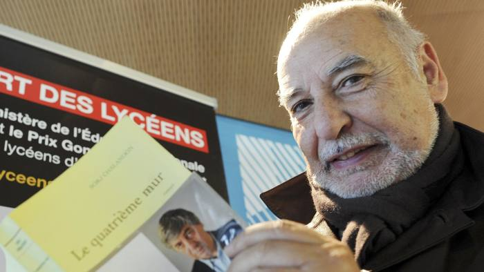 """Moroccan writer Tahar Ben Jelloun, who oversaw the Goncourt des Lyceens literary prize jury this year, poses with the winning novel """"Le quatrième mur"""", written by French journalist and author Sorj Chalandon on November 14, 2013, in Rennes. The 'Goncourt des Lyceens' (Goncourt of high school students) is similar to the famous Prix Goncourt, however its' jury is comprised of French high-school students. AFP PHOTO / JEAN-FRANCOIS MONIER (Photo credit should read JEAN-FRANCOIS MONIER/AFP/Getty Images)"""