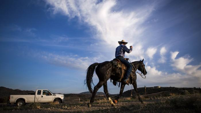 Bart Steninger salutes a member of their caravan during a 320-mile relay horseback ride from Elko, Nevada to the State Capitol in Carson City to deliver a petition to Governor Brian Sandoval, May 29, 2014. The ranchers want Sandoval?s help in ousting a regional Bureau of Land Management official whose office in northern Nevada has reduced by 20 percent the number of cattle allowed to graze over the next 12 months in the Battle Mountain region east of Carson City, citing lingering drought. Picture taken May 29, 2014. REUTERS/Max Whittaker (UNITED STATES - Tags: POLITICS BUSINESS AGRICULTURE ENVIRONMENT) - RTR3RLC3