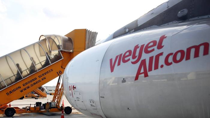 Passengers disembark a VietJet Air aircraft, operated by VietJet Aviation Joint Stock Co., at Tan Son Nhat International Airport in Ho Chi Minh City, Vietnam, on Monday, Jan. 9, 2017. VietJet, the Vietnam carrier known for its bikini-clad flight attendants, expects profit to surge 30 percent this year on rising passengers as it prepares for its Ho Chi Minh City Stock Exchange listing debut in February. Photographer: Linh Luong Thai/Bloomberg