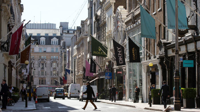 Members of the public walk past luxury goods retailers on Old Bond Street on April 15, 2014 in London, England