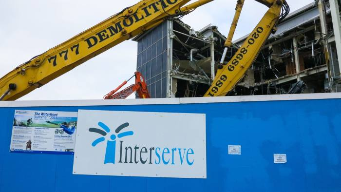 D5WTHE Yellow demolition crane indicates towards Interserve sign