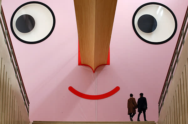 """People walk at the entrance of the """"Giro Giro Tondo design for children"""" exhibition, at the Triennale museum, in Milan, Italy, Monday, April 3, 2017. The Milan Design week is taking place in various locations across Milan from April 4 through 9, 2017. (i)"""