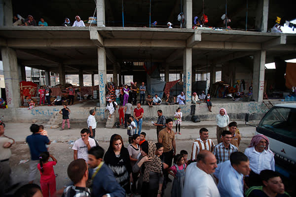 Yazidi families take refuge in an abandoned building near Dohuk