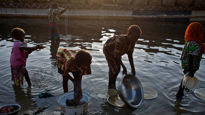 Girls use the waters of Lake Chad to do the washing