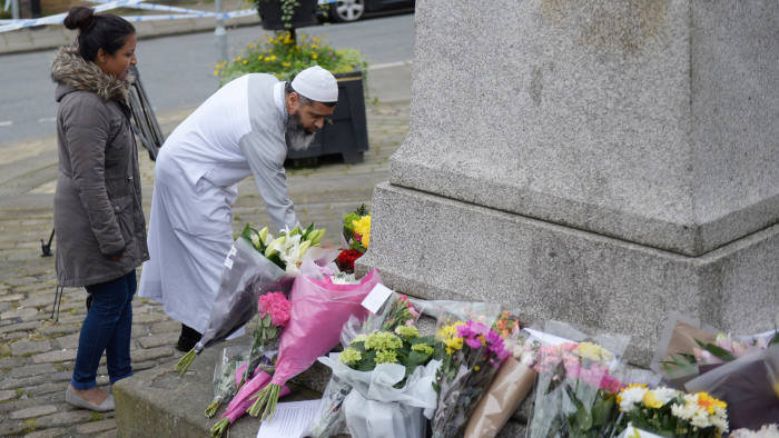 """A man arrives to lay floweres at a statue to Joseph Priestly in Birstall, northern England, on June 17, 2016, near to the scene where Labour MP Jo Cox was shot yesterday. Jo Cox, the British lawmaker murdered on the streets of northern England on June 16, had complained to police earlier this year about """"malicious communications"""" she received, police said Friday. / AFP PHOTO / OLI SCARFFOLI SCARFF/AFP/Getty Images"""