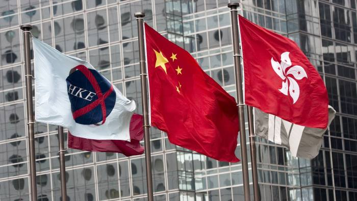 Hong Kong Exchanges And Clearing Ltd. Announces 2009 Annual Results...The flag of the Hong Kong Exchanges & Clearing Ltd., left, the Chinese flag, center, and the Hong Kong SAR flag, fly outside Hong Kong Exchanges & Clearing Ltd., in Hong Kong, China, on Thursday, March 4, 2010. Hong Kong Exchanges & Clearing Ltd., the operator of Asia's third-biggest stock market, posted an 8 percent drop in profit last year, in line with analyst estimates, as trading decreased amid a global slump. Photographer: Jerome Favre/Bloomberg