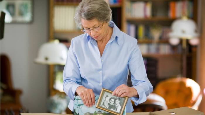 Senior woman packing picture frame in a cardboard box...D9HFYC Senior woman packing picture frame in a cardboard box