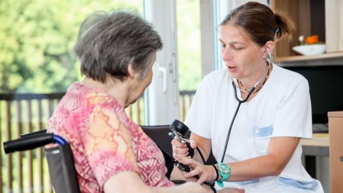 Nurse Checking Blood Pressure of Senior Female Patient on Wheelchair